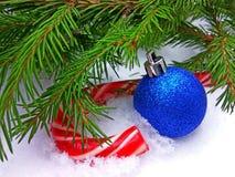 Het blauwe Nieuwjaarbal en suikergoed van de Kerstmiskaramel met groene spar op sneeuwachtergrond stock foto