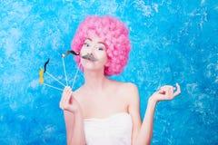 Het blauwe oog grappige meisje/de vrouw/de tiener met roze krullende pruik zijn wij stock foto