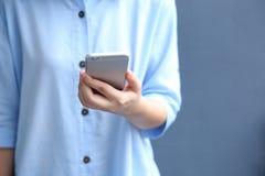 Het blauwe overhemd van de vrouwenkleding met het gebruiken van smartphone Stock Afbeelding