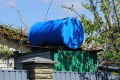 Het blauwe plastic vat ligt buiten op de structuur voor de douche in de yard stock foto