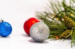 Het blauwe, rode, zilveren close-up van de Kerstmisbal tegen pijnboomnaalden B Stock Afbeelding