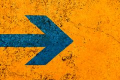 Het blauwe teken van de pijlrichting over de levendige heldere oranje muur van de kleurensteen met onvolmaaktheden en barsten stock foto