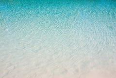 Het blauwe water golft wit zand stock foto's