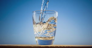 Het blauwe water stroomt in het glas vormt bellen en plonsen stock footage
