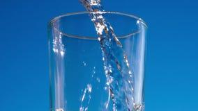 Het blauwe water stroomt in het glas vormt bellen en plonsen stock videobeelden