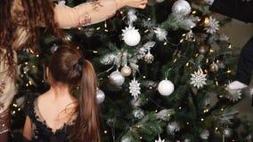 Het blije echtpaar met hun kinderen verfraait Kerstboom in huis stock videobeelden