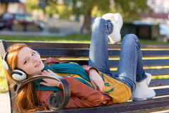 Het blije het glimlachen meisje ontspannen op bank in park die hoofdtelefoons met behulp van Stock Foto