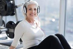 Het blije hogere vrouw ontspannen in hoofdtelefoons na training Royalty-vrije Stock Afbeelding