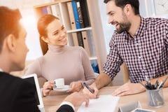 Het blije jonge paar ondertekent contract voor aankoop van nieuw huis in bureau van makelaardij stock fotografie
