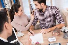 Het blije jonge paar ondertekent contract voor aankoop van nieuw huis in bureau van makelaardij stock foto's