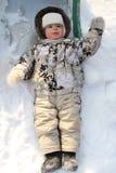 Het blije kind legt op een sneeuw royalty-vrije stock fotografie