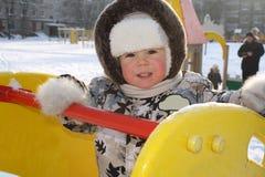 Het blije kleine kind op een speelplaats stock afbeelding