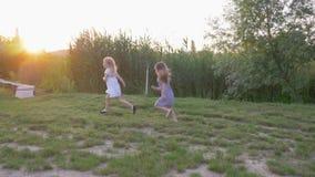 Het blije kleine spel van vriendenmeisjes loopt en loopt op groene weide in helder zonlicht de achterstand in stock videobeelden