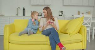 Het blije meisje heeft aandacht van haar bezige mum nodig stock video
