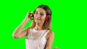 Het blije meisje in hoofdtelefoons luistert muziek en dansen bij groene achtergrond stock videobeelden