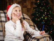 Het blije meisje schrijft een brief aan Santa Claus royalty-vrije stock foto's