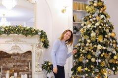 Het blije meisje verfraait Kerstboom en treft voor vakantie o voorbereidingen Stock Afbeeldingen