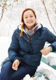 Het blije mooie meisje zit op de bank in de winterpark Royalty-vrije Stock Afbeeldingen
