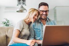 Het blije paar ontspant en werkt aan laptop computer bij moderne woonkamer stock afbeeldingen