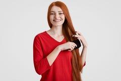 Het blije redhaired wijfje met charmante glimlach, kamt haar foxy haar, heeft freckled gezicht, gekleed in rode die sweater, over royalty-vrije stock afbeeldingen