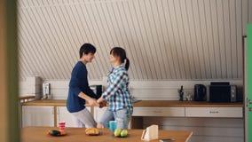 Het blije studenten mooie paar danst en heeft pret in keuken die samen en van vrije tijd genieten lachen stock videobeelden