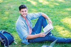 Het blije universitaire leven Leuke mannelijke student die een boek en loo houden Stock Foto's