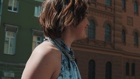 Het blije vocalistmeisje presteert in oude stad in de zomerkleding stock footage