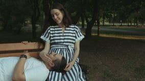Het blije zwangere paar plakken in openbaar park stock videobeelden