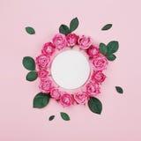 Het bloemendiekader van witte spatie wordt gemaakt, roze nam bloemen en groene bladeren op pastelkleur hoogste mening als achterg stock afbeeldingen