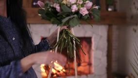 Het bloemistmeisje houdt in haar hand een gebeëindigd boeket van rozen en installaties op lange stammen, strak bindend het boeket stock video