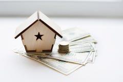 Het blokhuis bevindt zich op een stapel van document rekeningendollars als symbool van hypotheek op witte achtergrond Het geld va royalty-vrije stock afbeelding