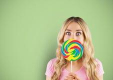 Het blond-haarmeisje hidded door een suikergoed met groene achtergrond Stock Foto's