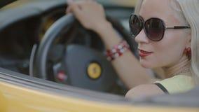 Het blonde is achter het wiel van cabriolet aanwezig stock footage