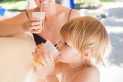 Het blonde babymeisje met moeder drinkt jus d'orange Royalty-vrije Stock Afbeelding