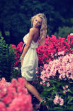 Het blonde dame stellen in bloemen royalty-vrije stock afbeeldingen