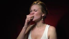 Het blonde in een wit overhemd smeert zich met room en scheurt de doughnut met haar tanden stock videobeelden