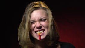 Het blonde in een zwart jasje lacht en eet een jellyworm stock videobeelden