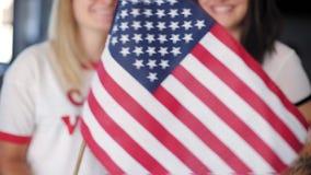 Het blonde en de donkerbruine hipstermeisjes houden een vlag stock footage