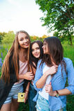 Het blonde en het brunette die van drie hipstersmeisjes zelfportret op polaroidcamera en openlucht glimlachen nemen Meisjes die p Stock Foto's