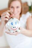 Het blonde geld van de vrouwenbesparing in een piggy-bank stock fotografie
