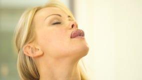 Het blonde glimlacht en trekt haar tong aan de neus stock video