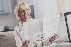 Het blonde-haired artikel van de vrouwenlezing in de hotelruimte royalty-vrije stock fotografie