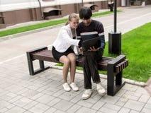 Het blonde-haired volwassen meisje in glazen, die toont iets op laptop aan een donkerharige, die op een bank zitten glimlachen Me royalty-vrije stock afbeeldingen