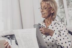 Het blonde-haired vrouw het drinken artikel van de koffielezing royalty-vrije stock afbeelding
