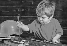 Het blonde jong geitje spelen in workshop Jongens bindende schroeven aan houten raad Geconcentreerd kind die nieuwe vaardigheden  royalty-vrije stock foto