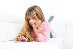 Het blonde jong geitjemeisje spelen met tabletpc op witte bank stock afbeeldingen