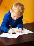 Het blonde jonge geitje van het jongenskind met pen die op stuk van document schrijven. Thuis. Stock Foto