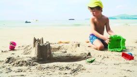 Het blonde jongen spelen met zand op een strand in Thailand stock videobeelden