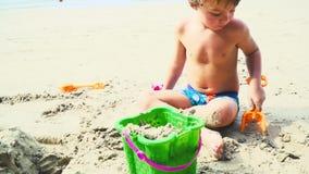 Het blonde jongen spelen met zand op een strand in Thailand stock footage