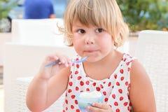 Het blonde Kaukasische babymeisje eet bevroren yoghurt Stock Afbeelding